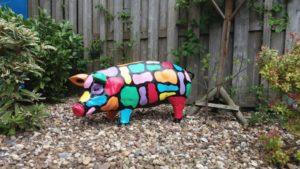 polyester beeld van een beschilderd varken als kunstobject in de tuin