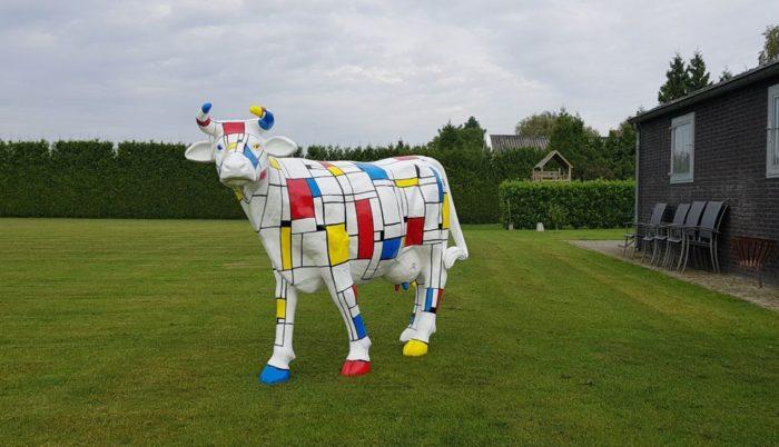 Vrolijke beelden Een levensgrote koe beschilderd in Piet Mondriaan kleuren en motieven