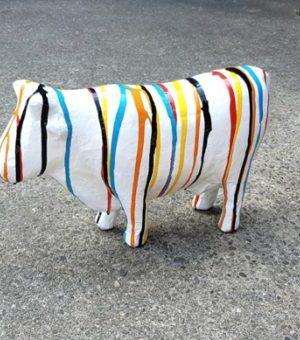 Papier maché beeld van een witte koe met verfsputters