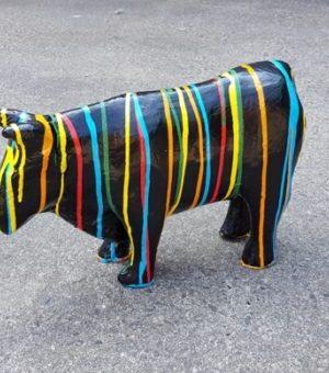Papier maché beeld van een zwarte koe met verfsputters