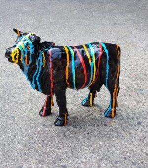 Polyester beeldje van een zwart koetje met verfsputters