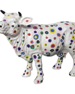 Beeldje van een wit kunststof koetje met gekleurde stippen vrolijke beelden