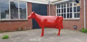 Een polyester beeld van een koe in rode verf geschilderd