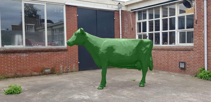 Beeld van een kunststof koe in groene verf