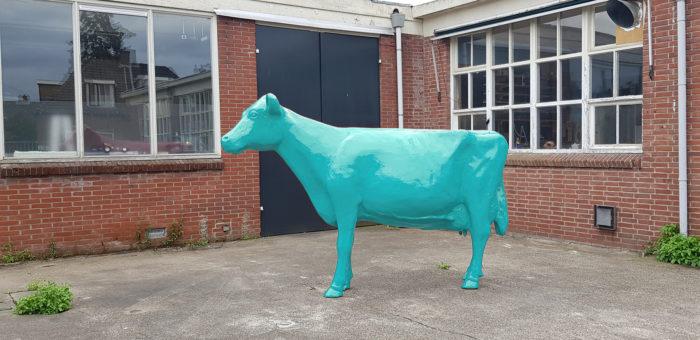 Polyester koe in blauwe verf geschilderd.