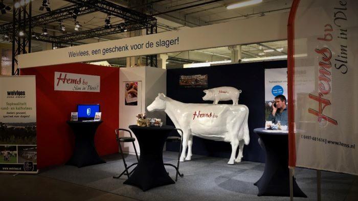 Kunststof beelden van een koe en varken met het logo van Hems Bv