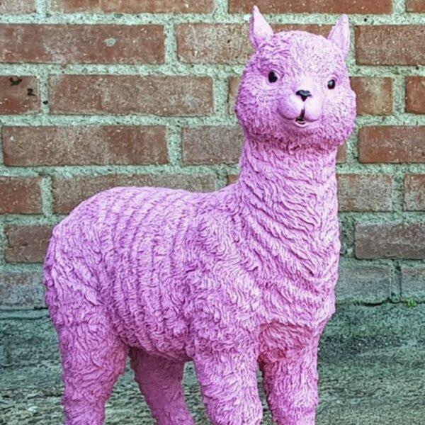 Een polyester beeldje van een roze alpaca