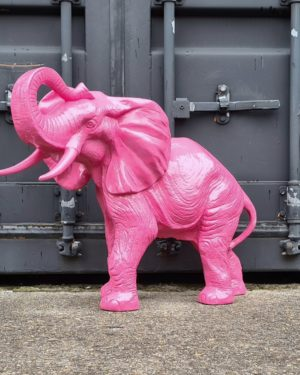 tuinbeeld van een roze olifant met de slurf omhoog