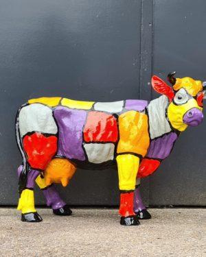 Designobjecten in tuin, polyester dierenbeelden. Beelden van beschilderde kunststof koeien en kalveren